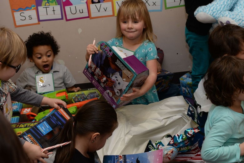 Children tear open presents from Santa inside the Youth & Family Services Child Development Center in Rapid City, S.D., Dec. 19, 2017. This event has been hosted by the 28th Operations Group for 11 years. (U.S. Air Force photo by Airman 1st Class Nicolas Z. Erwin)