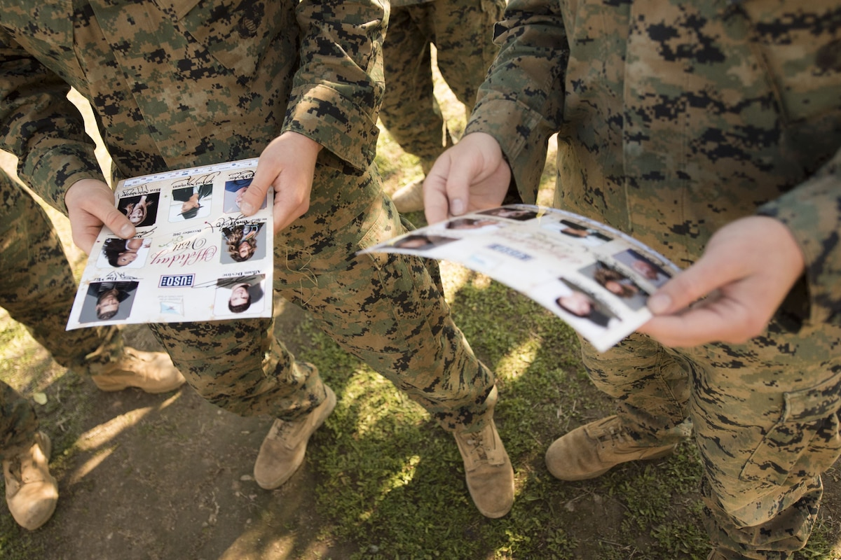 Service members hold a flyer with photos on it.