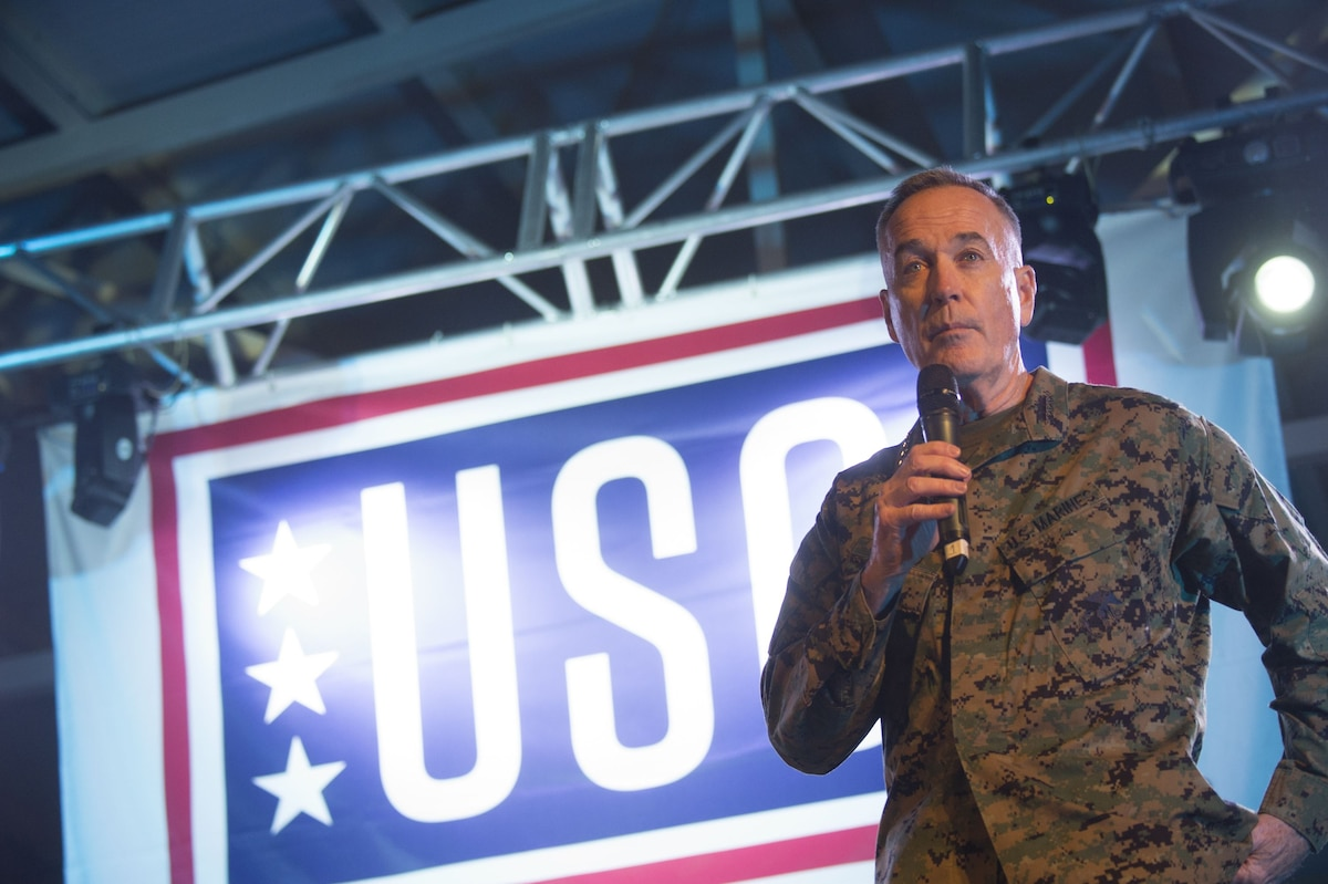 Marine Corps Gen. Joe Dunford speaks on a mic in front of a USO sign.