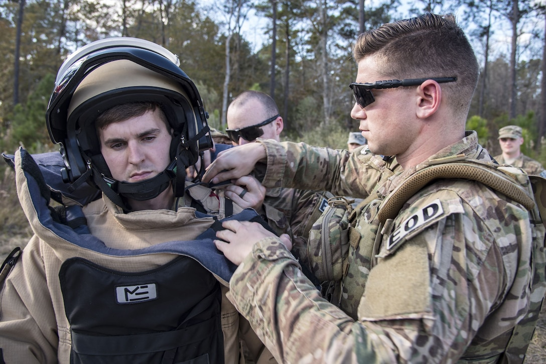 Senior Airman Trenton Broxterman, right, 23d Civil Engineer Squadron (CES) Explosive Ordinance Disposal (EOD) apprentice, adjusts a body suit for Tech Sgt. Nick Adkisson, 23d CES EOD team leader, during a response training exercise, Dec 21, 2017, at Moody Air Force Base, Ga.  The EOD Airmen were evaluated on their ability to respond to a distress call, locate, identify and neutralize an improvised explosive device. (U.S. Air Force photo by Airman Eugene Oliver)