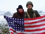 Army Maj. Tracy Yates and a reenactor portraying a U.S. Army soldier who fought in the Battle of the Bulge pose with a period-correct 48-star American flag, Dec. 16 near Bastogne, Belgium. (Photo courtesy DLA Europe & Africa)