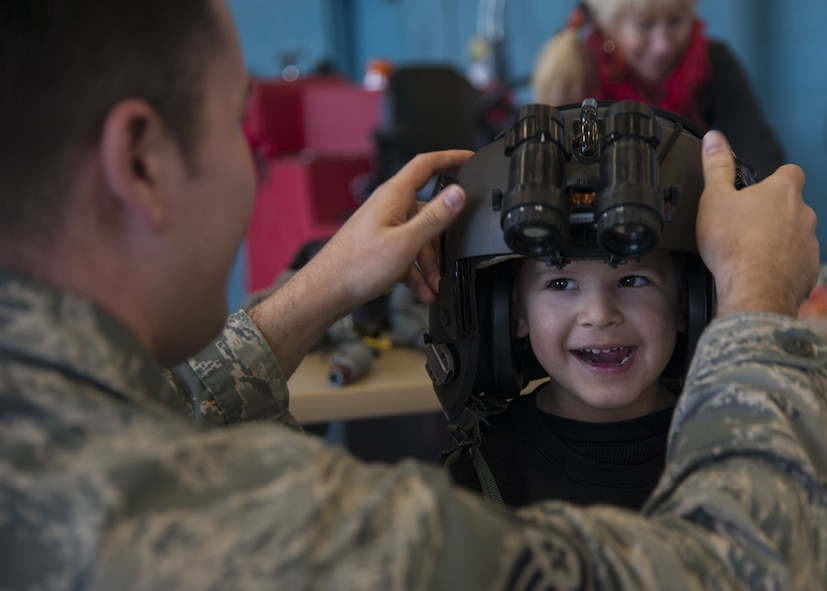 U.S. Air Force Staff Sgt. Mark Guereque, 58th Operations Support Squadron aircrew flight equipment journeymen, adjusts the visor on a helmet for a visitor from the Presbyterian and University of New Mexico children's hospital at Kirtland Air Force Base, N.M., Dec. 21.