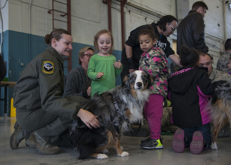 Tech. Sgt. Megan Freeman, 415th Special Operations Squadron first sergeant, pets a puppy with visitors from the Presbyterian and University of New Mexico children's hospital at Kirtland Air Force Base, N.M., Dec. 21.