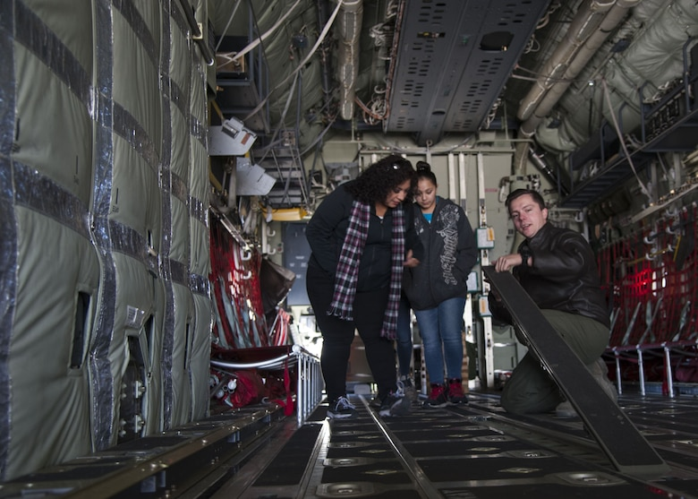 Staff Sgt. Zach Harmon, 58th Special Operations Wing MC-130J loadmaster, demonstrates how to change floor panels on the MC-130J to visitors from the Presbyterian and University of New Mexico children's hospital, at Kirtland Air Force Base, N.M., Dec. 21.