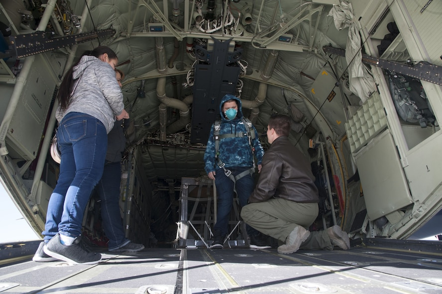 Staff Sgt. Zach Harmon, 58th Special Operations Wing MC-130J aircraft loadmaster, fits a visitor from the Presbyterian and University of New Mexico children's hospital in a parachute aboard a MC-130J, at Kirtland Air Force Base, N.M., Dec. 21.
