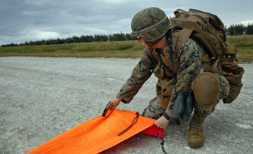 Marine Corps Cpl. Kate Mazzone, a communications technician, secures a panel that will notify an aircraft where to land during Exercise Voodoo Magic on Iejima Island in Okinawa, Japan.