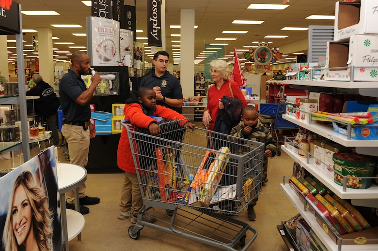 """U.S. Air Force Special Agents Joseph Cisneros and Brandon Smith, assigned to Air Force Special Investigations at Detachment 201, partner with Chase Frost, age 8 and Noah Frost, age 6, during the """"Shop with a Cop"""" event at Joint Base Langley-Eustis, Va., Dec. 19, 2017"""