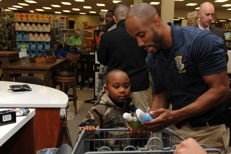 """U.S. Air Force Special Agent Brandon Smith, assigned to Air Force Special Investigations at Detachment 201, and mentee Noah Frost, age 6, check-out during the """"Shop with a Cop"""" event at Joint Base Langley-Eustis, Va., Dec. 19, 2017."""