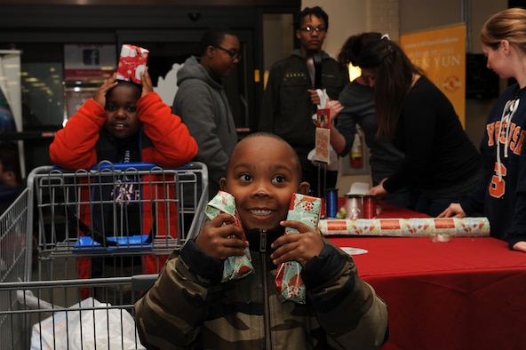 "Chase Frost, age 8 and Noah Frost, age 6, local youth with The Up Center's Team Up mentoring program, a non-profit organization in Hampton Roads, show-off gifts they purchased during the ""Shop with a Cop"" event at Joint Base Langley-Eustis, Va., Dec. 19, 2017."