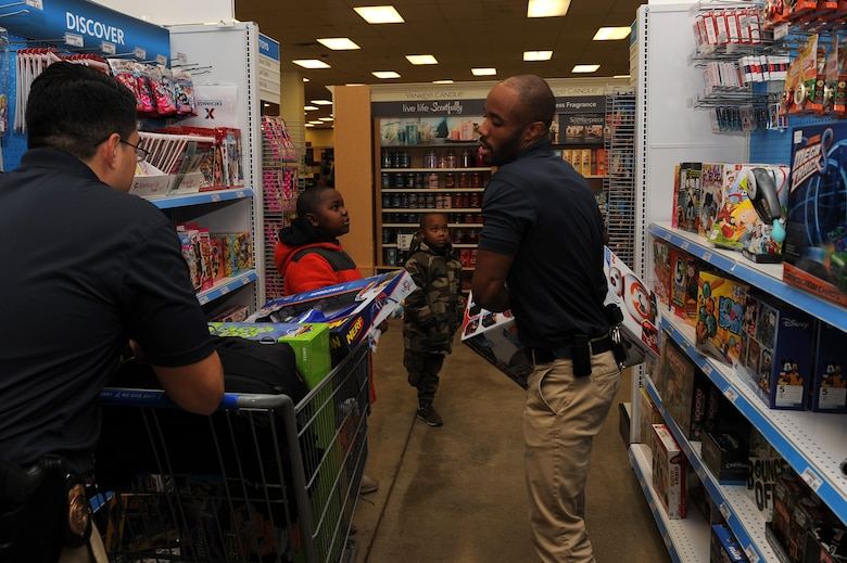 """U.S. Air Force Special Agents Joseph Cisneros and Brandon Smith, assigned to Air Force Special Investigations at Detachment 201, partner with Chase Frost, age 8 and Noah Frost, age 6, during the """"Shop with a Cop"""" event at Joint Base Langley-Eustis, Va., Dec. 19, 2017."""