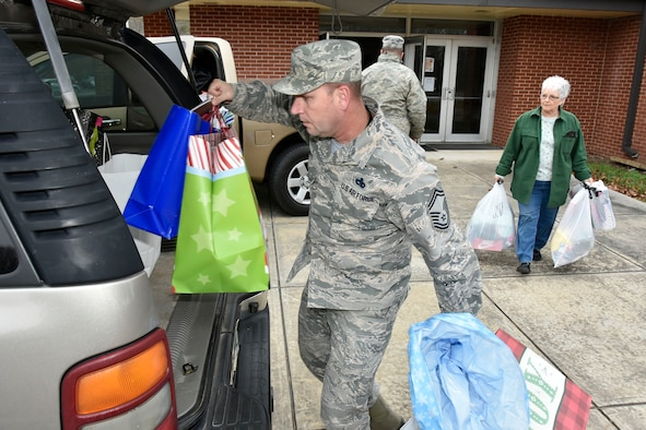 Senior Master Sgt. Charles Hoyt, with the AEDC Arnold Air Force Base Test Systems Sustainment Division, and a community volunteer collect the toys and clothing donated through this year's Arnold AFB Angel Tree program. The items provided by base personnel will go to 143 area children. (U.S. Air Force photo/Rick Goodfriend)