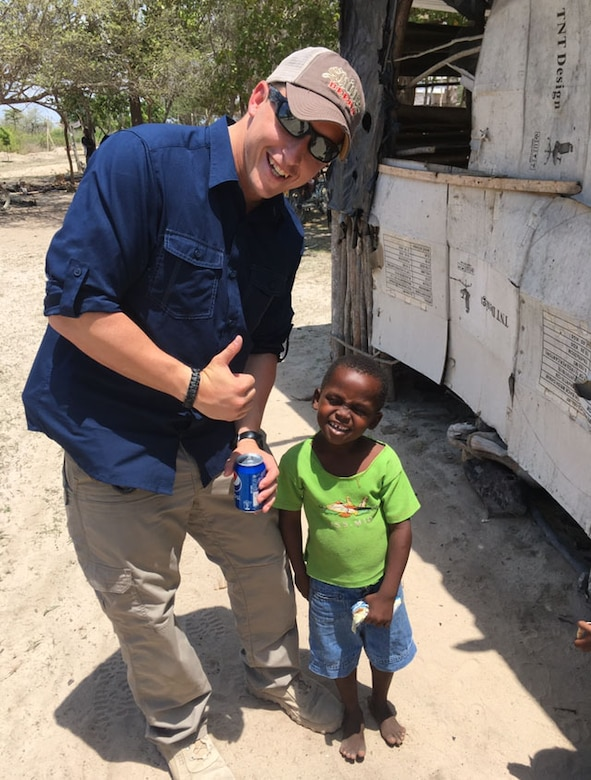 Image of Senior Airman John Dantoni, 366th Security Forces Response Force member, smiles with a child in a Kenyan village. Before this picture was taken, Dantoni taught the child how to open a soda. (Photo courtesy of SrA John Dantoni)