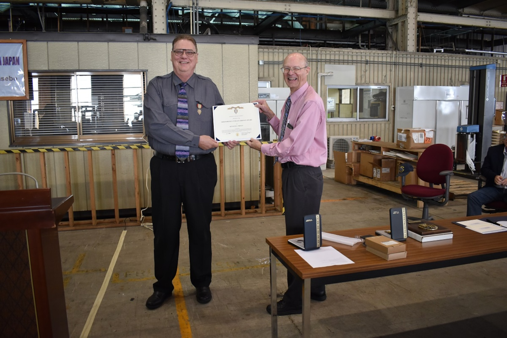 Roy Jewell (right), acting director DLA Distribution Yokosuka Japan presents Joe Pirman with his retirement awards during a town hall on Dec. 4.
