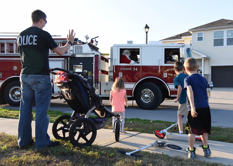 Santa throws candy to children from a fire truck in Bay Ridge housing Dec. 21, 2017, on Keesler Air Force Base, Mississippi. Santa and fire department members drove through each housing area to spread Christmas cheer to Airmen and their families. (U.S. Air Force photo by Kemberly Groue)