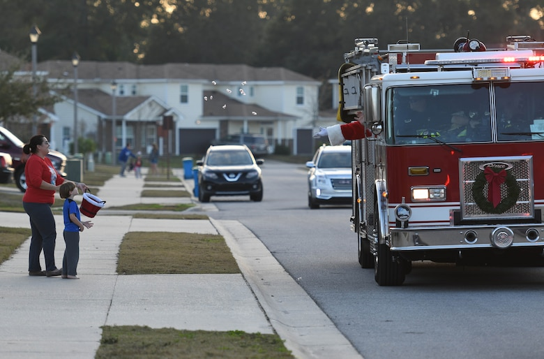 Santa throws candy to Nicole and Luke Stillwagon, family of Master Sgt. Joshua Stillwagon, 334th Training Squadron instructor supervisor, from a fire truck in Bay Ridge housing Dec. 21, 2017, on Keesler Air Force Base, Mississippi. Santa and fire department members drove through each housing area to spread Christmas cheer to Airmen and their families. (U.S. Air Force photo by Kemberly Groue)