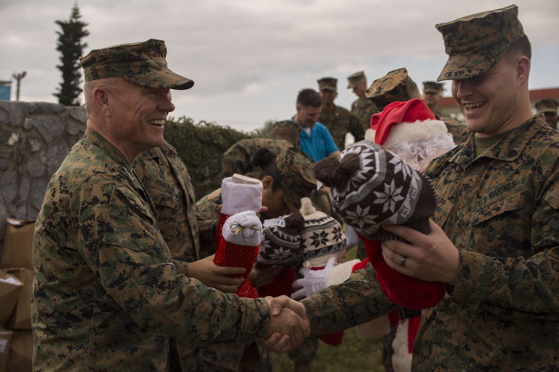 Lt. Gen. Lawrence D. Nicholson, the commanding general of III Marine Expeditionary Force, hands out Christmas stockings to Marines at Camp Courtney, Okinawa, Japan, Dec. 22, 2017.  Nicholson, alongside Santa Claus, wished the Marines happy holidays and provided gifts from volunteer organizations to the III MEF command element to spread Christmas cheer.