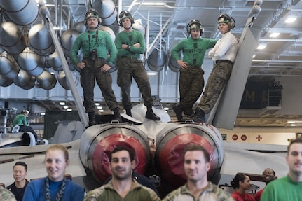 Marines watch a USO show from the top of an F/A-18F Super Hornet.