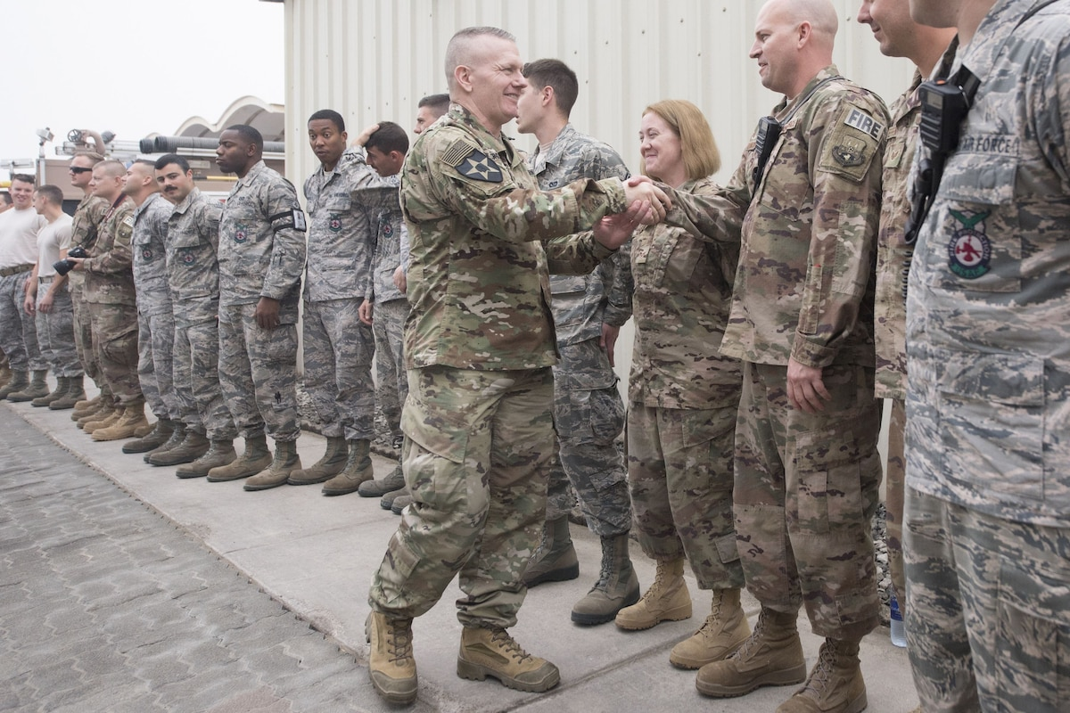 Army Command Sgt. Maj. John W. Troxell shakes hands with a service member standing outside in a row of troops.