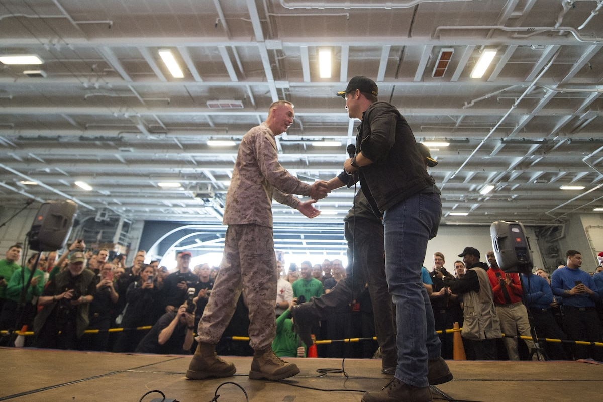 Marine Corps Gen. Joe Dunford shakes hands with Adam Devine on a stage as an audience of sailors watches.