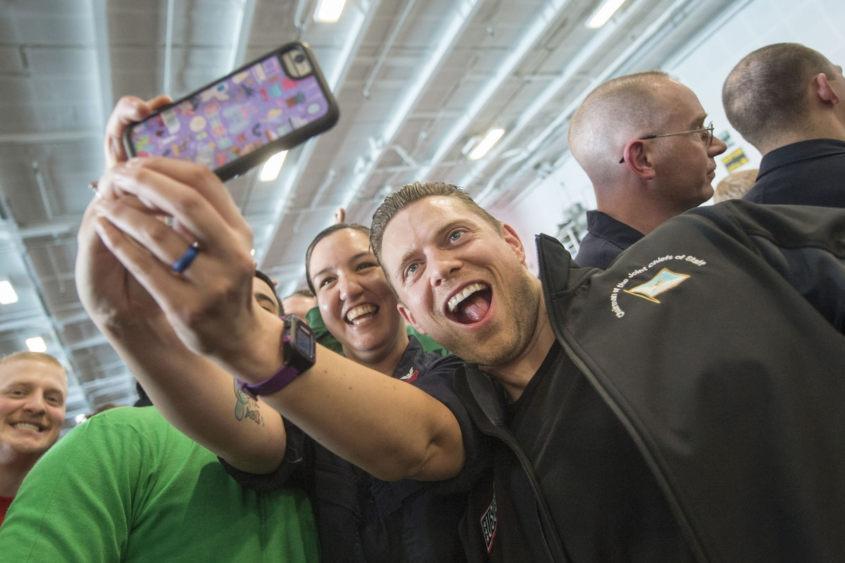 """A woman smiles and holds a cell phone in front of her while taking a selifie with WWE Superstar """"The Miz."""""""