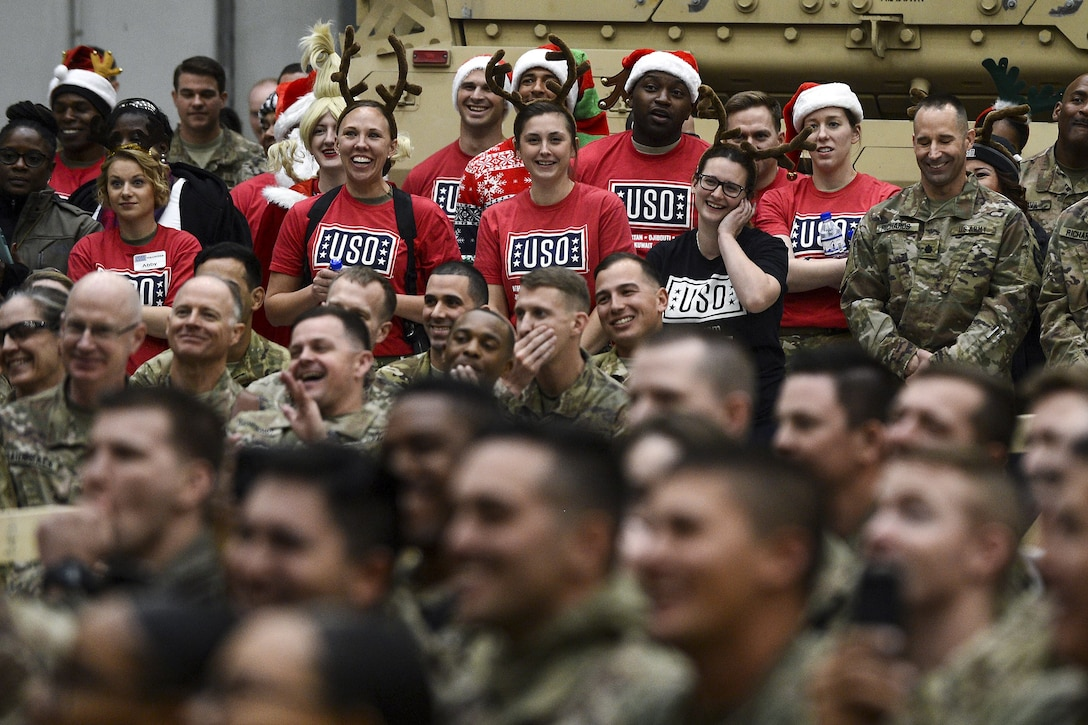 An audience of service members, some in USO shirts and holiday garb, laugh.