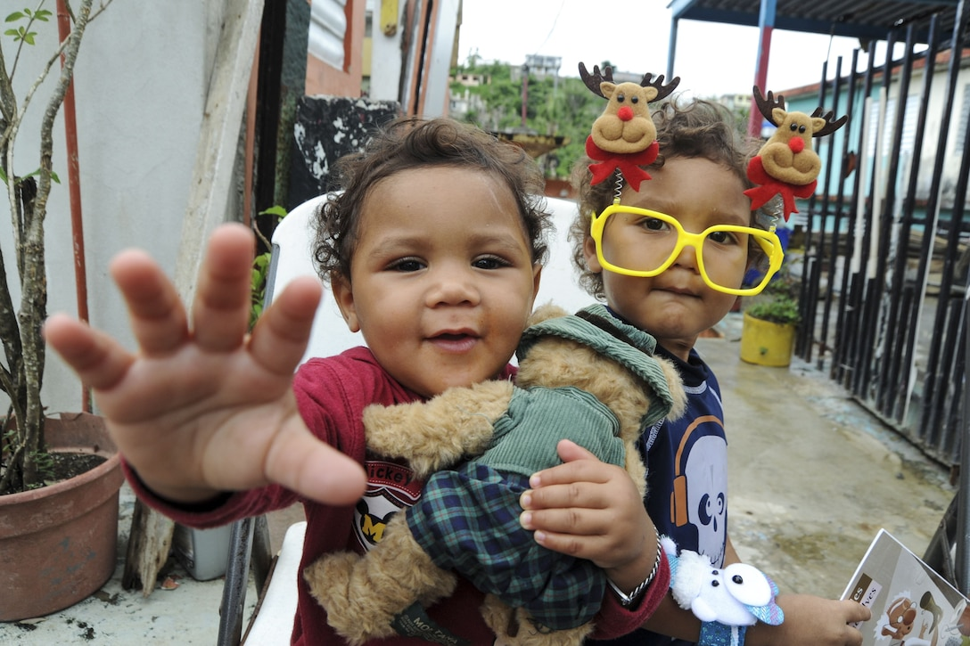 A child holding a stuffed animal reaches toward the camera, while another one wearing Christmas novelty glasses looks on.