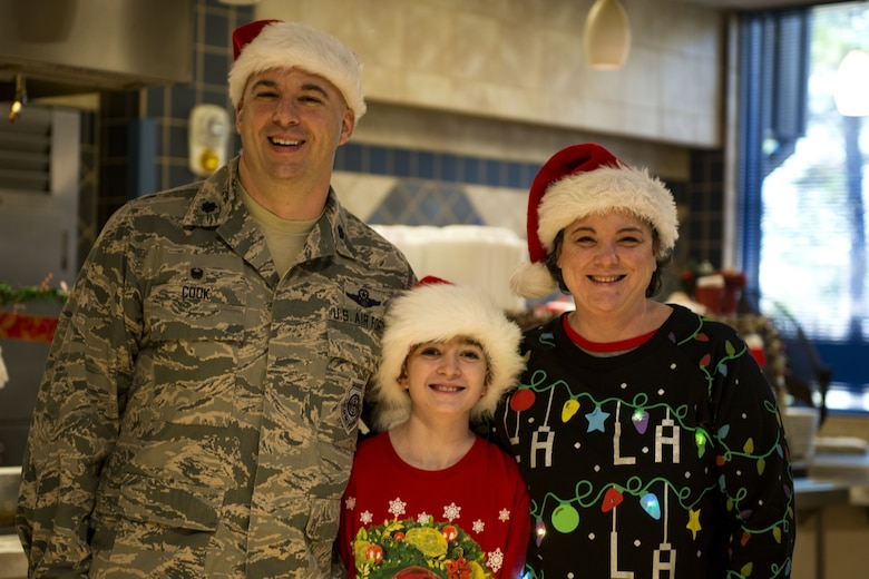 Lt. Col. Gerald Cook, left, 76th Fighter Squadron commander, his son, Justin, middle, and his wife, Catherine, right, pose for a photo on Christmas Day in the Georgia Pines Dining Facility, Dec. 25, 2017, at Moody Air Force Base, Ga. The Christmas meal was an opportunity for Airmen, retirees, dependents and leadership to enjoy a traditional Christmas meal. (U.S. Air Force photo by Airman 1st Class Erick Requadt)
