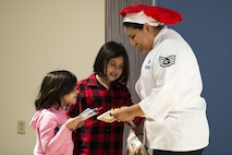 Staff Sgt. Anna Peterson, 23d Force Support Squadron dining facility manager, opens a gift from her daughters on Christmas Day in the Georgia Pines Dining Facility, Dec. 25, 2017, at Moody Air Force Base, Ga. The Christmas meal was an opportunity for Airmen, retirees, dependents and leadership to enjoy a traditional Christmas meal. (U.S. Air Force photo by Airman 1st Class Erick Requadt)