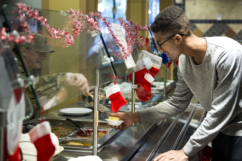 1st Lt. Lizette Wu, left, 822d Base Defense Squadron flight commander, serves Airman Darius Buggs, 23d Aircraft Maintenance Squadron crew chief, on Christmas Day in the Georgia Pines Dining Facility, Dec. 25, 2017, at Moody Air Force Base, Ga. The Christmas meal was an opportunity for Airmen, retirees, dependents and leadership to enjoy a traditional Christmas meal. (U.S. Air Force photo by Airman 1st Class Erick Requadt)