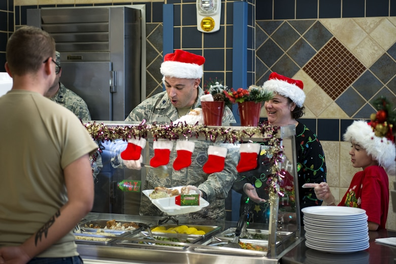 Lt. Col. Gerald Cook, right, 76th Fighter Squadron commander, serves Airman Jesse Lowe, 23d Security Forces Squadron fireteam member, on Christmas Day in the Georgia Pines Dining Facility, Dec. 25, 2017, at Moody Air Force Base, Ga. The Christmas meal was an opportunity for Airmen, retirees, dependents and leadership to enjoy a traditional Christmas meal. (U.S. Air Force photo by Airman 1st Class Erick Requadt)