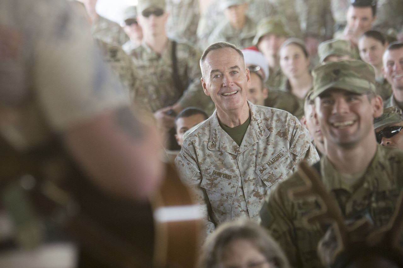 Marine Corps Gen. Joe Dunford listens to music in a crowd of service members.