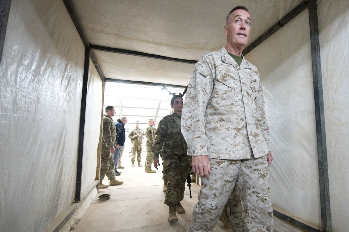 The chairman of the Joint Chiefs of Staff walks through a tunnel.