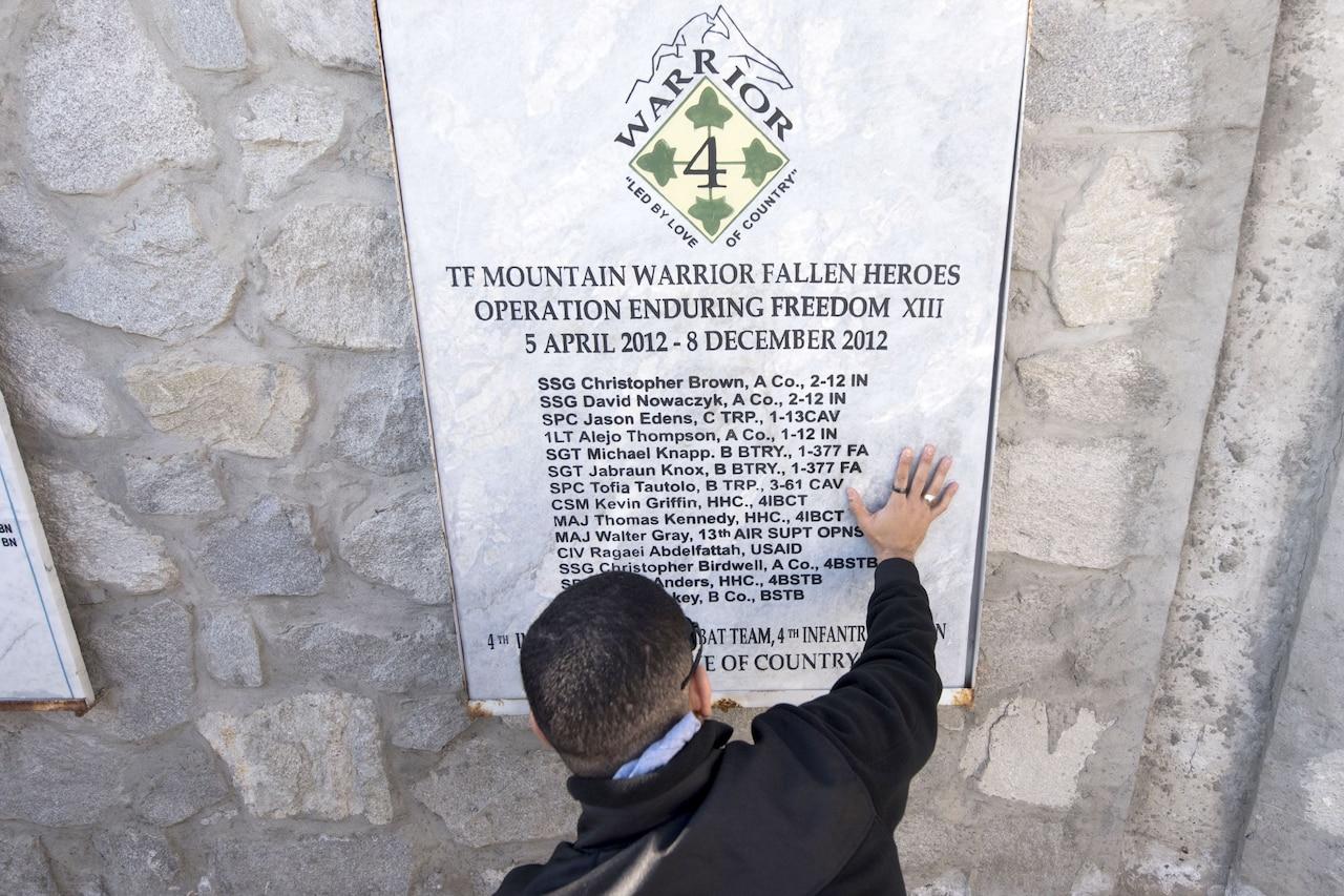 A Medal of Honor recipient kneels at a memorial.