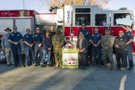 Col. Sekou Karega, commanding officer, Marine Corps Logistics Base Barstow, stands with Lucy Perez, president,  (left) and Emily Jenright ,vice president, of American Legion Auxiliary Leo Collins Unit 229, based in Adelanto, CA. On Dec. 19 members of the Ladies Auxiliary donated several boxes to the Toys for Tots campaign, which helps raise toys and funds in support of the local communities.