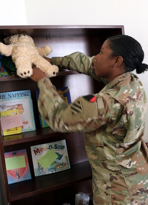Army Pfc. Hertaycious King, a religious affairs specialist with Special Troops Battalion, 3rd Infantry Division Resolute Support Sustainment Brigade, puts away books and toys at Bagram Airfield, Afghanistan.