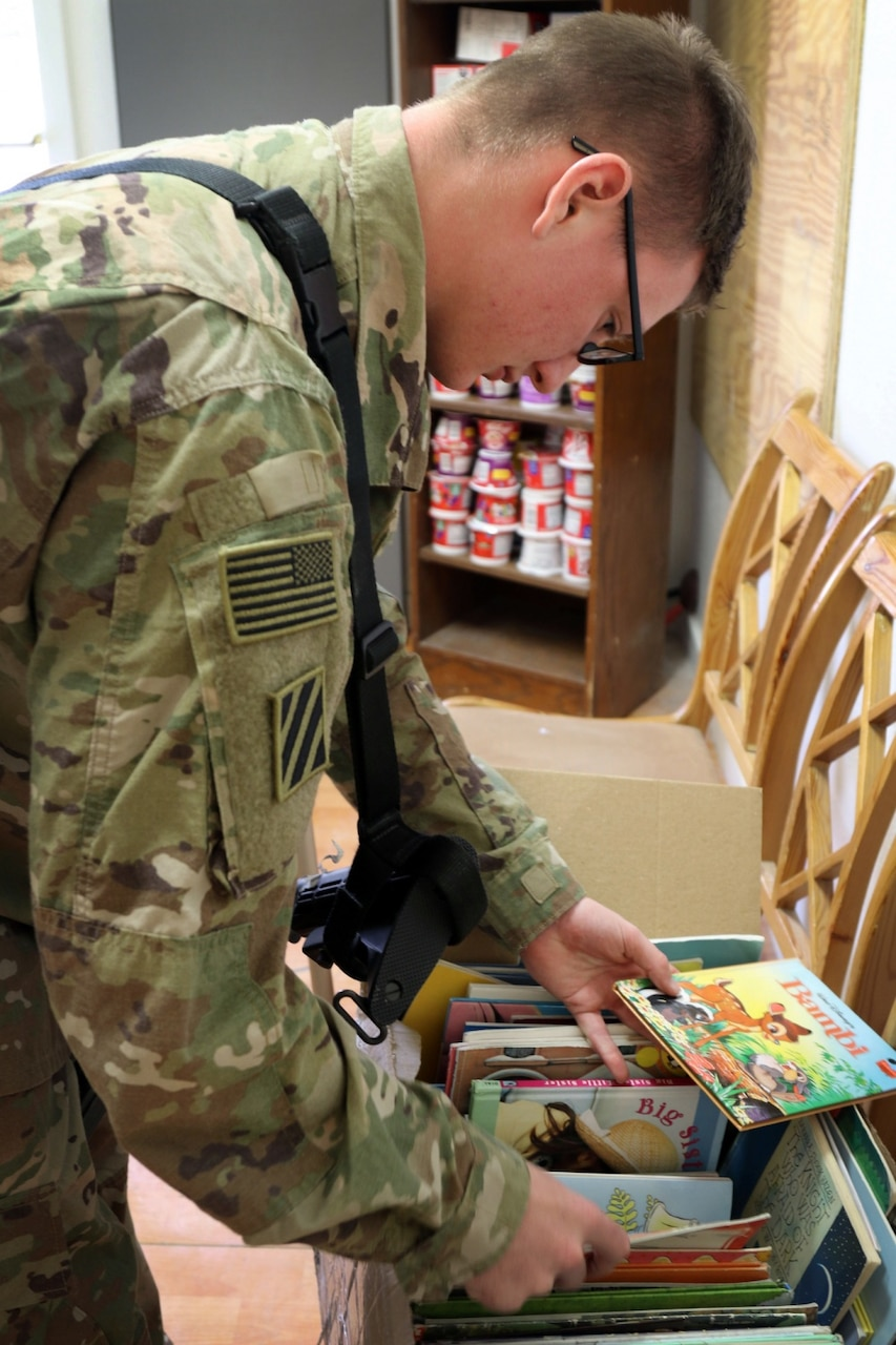 Army Pfc. Austin Callihan, an intelligence analyst with the 3rd Infantry Division Resolute Support Sustainment Brigade, picks out a book to read at Bagram Airfield, Afghanistan.