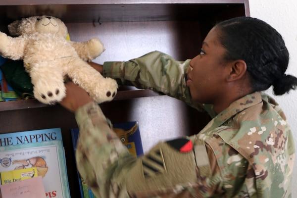 A soldier puts a stuffed bear on a book shelf.