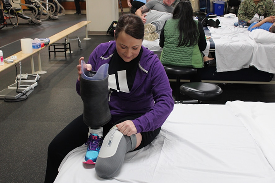 Maj. Stephanie Proellochs carefully inspects her leg and prosthesis after a round of physical therapy exercises at Walter Reed National Military Medical Center, Nov. 15, 2017. Proellochs underwent an amputation as a result of a malignant tumor that spread. (U.S. Air Force photo by Karina Luis)