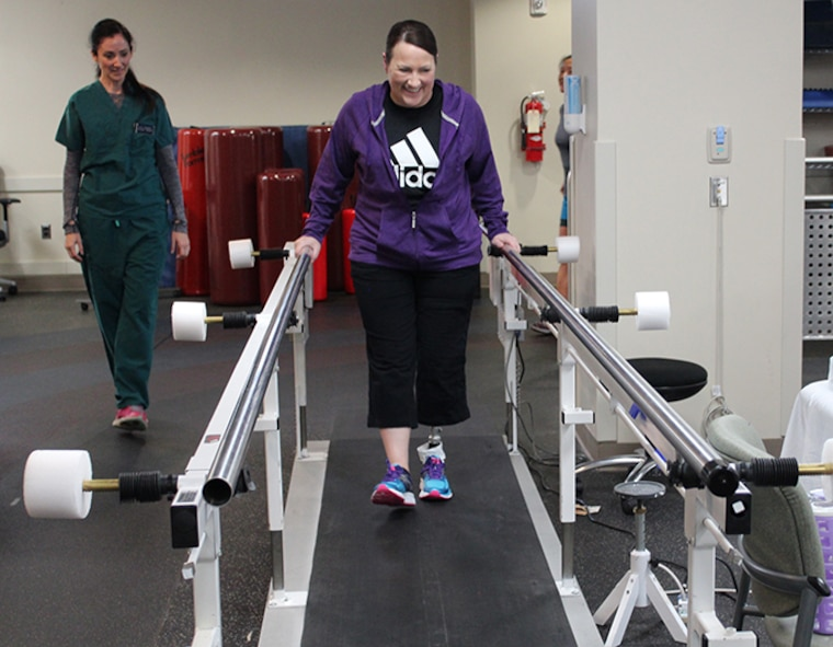 Maj. Stephanie Proellochs, a recent amputee, takes some of her first steps  in her new prosthesis, Nov. 15, 2017. During her physical therapy appointments, Proellochs engages in various exercises to ensure her comfort and safety with walking in a prosthesis. (U.S. Air Force by Karina Luis)