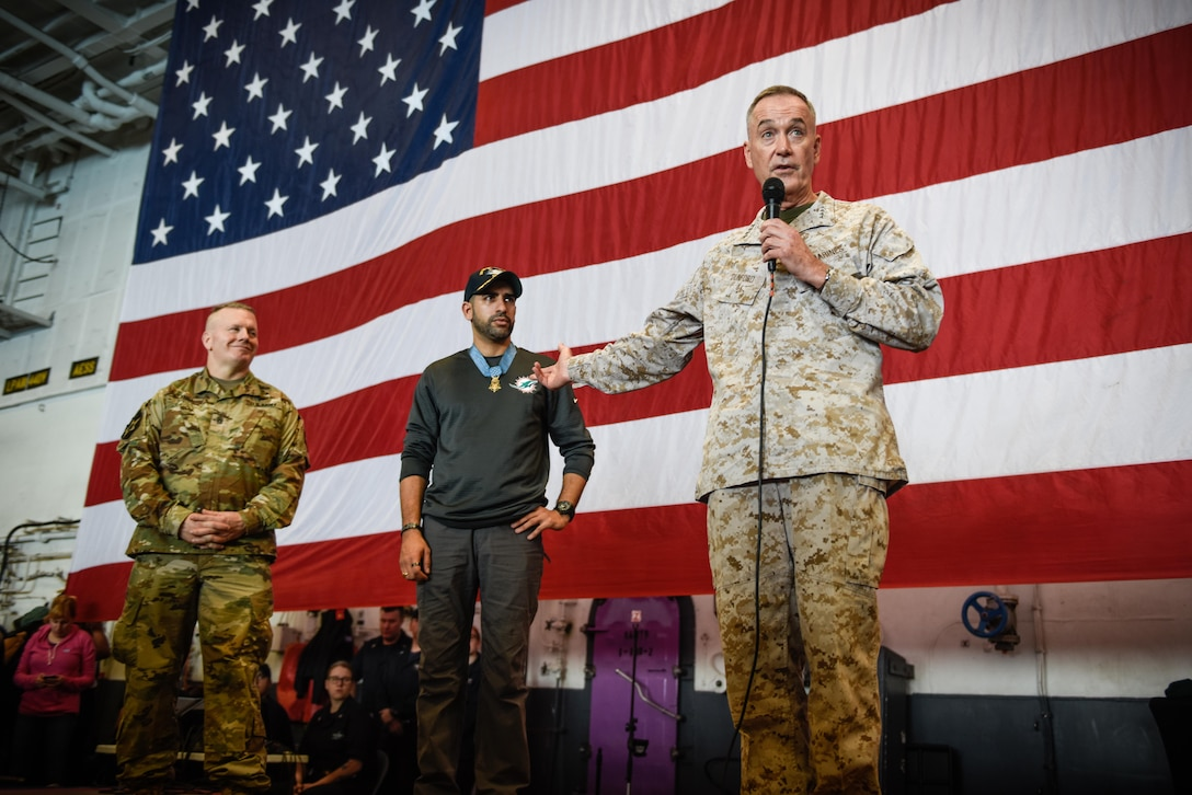 Dec. 23, 2017) The Chairman of the Joint Chiefs of Staff, U.S. Marine Corps Gen. Joe Dunford, right, introduces retired U.S. Army Capt. Florent Groberg, Medal of Honor recipient, and Command Sergeant Major John Troxell, the senior enlisted advisor to the Chairman of the Joint Chiefs of Staff, during a USO-sponsored visit aboard the aircraft carrier USS Theodore Roosevelt (CVN 71). For more than 75 years, the USO has provided a vital connection between service members, their families and the American people. The USO is a private, non-profit organization that seeks to strengthen America's military by keeping them connected to their family and nation. Theodore Roosevelt and its carrier strike group are deployed to the U.S. 5th Fleet area of operations in support of maritime security operations to reassure allies and partners and preserve the freedom of navigation and the free flow of commerce in the region. (U.S. Navy photo by Mass Communication Specialist 3rd Class Alex Perlman/Released)