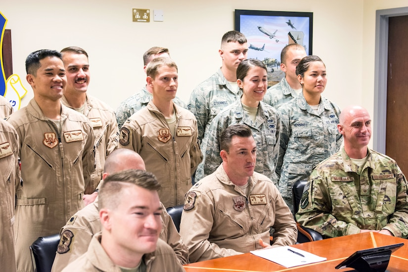 Service members stand and sit behind a desk.
