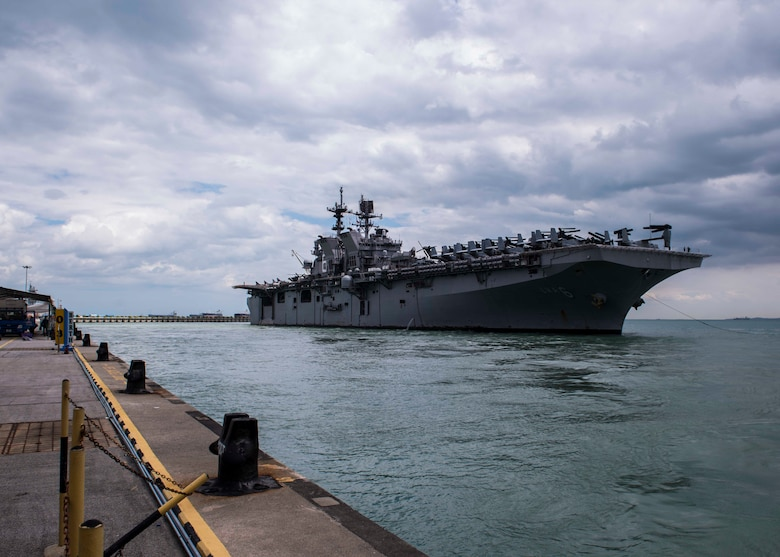 The amphibious assault ship USS America (LHA 6) pulls in to RSS Singapura - Changi Naval Base, Singapore during a regularly scheduled port visit Dec. 22. America, part of the America Amphibious Ready Group, with embarked 15th Marine Expeditionary Unit, is operating in the Indo-Asia Pacific region to strengthen partnerships and serve as a ready-response force for any type of contingency