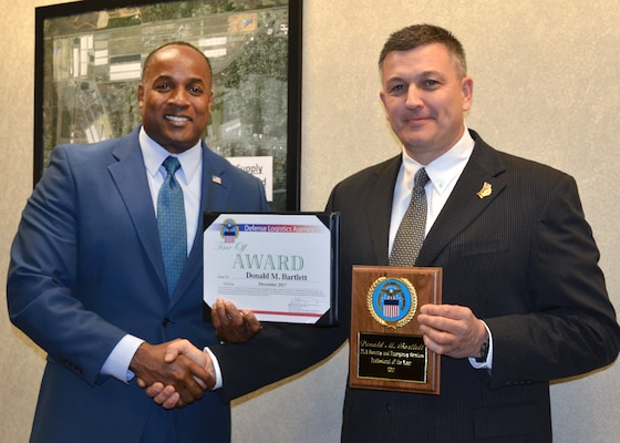 Donald Bartlett (right) receives the first Security Professional of the Year Award from Patrick Wright, staff director of Security and Emergency Services at DLA HQ.