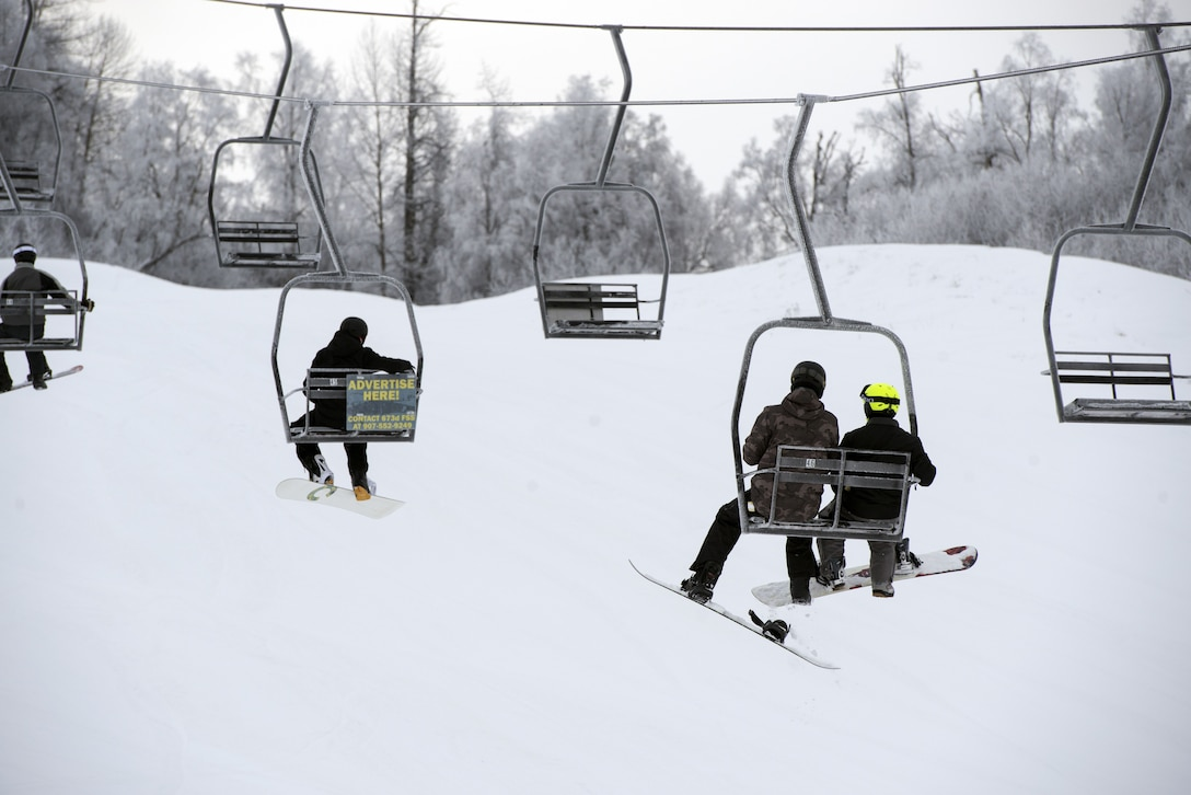 Snowboarders board a lift at the Hillberg Ski Area during Winterfest at Joint Base Elmendorf-Richardson, Alaska, Dec. 21, 2017. Winterfest was a winter solstice celebration hosted by Hillberg for anyone with base access and offered a plethora of events from noon to as late at 8 p.m.