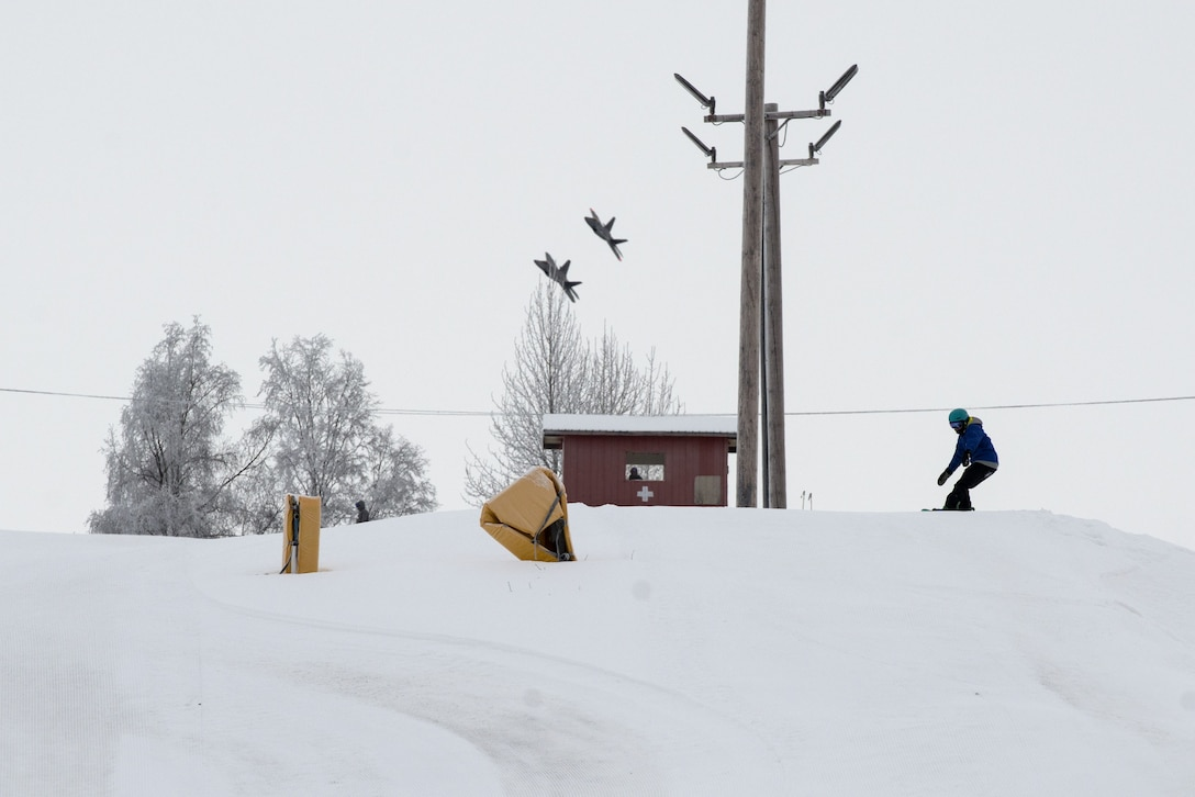 A snowboarder prepares to go down Hillberg Ski Area with F-22 Raptors in the background during Winterfest at Joint Base Elmendorf-Richardson, Alaska, Dec. 21, 2017. Winterfest was a winter solstice celebration hosted by Hillberg for anyone with base access and offered a plethora of events from noon to as late at 8 p.m.