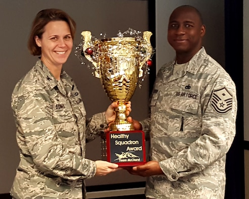 Col. Sonkiss, 62nd Airlift Wing commander, left, presents Master Sgt. Benjamin Harrison, 4th Airlift Squadron first sergeant, with the Healthy Squadron Award trophy Dec. 13, 2017, at Joint Base Lewis-McChord, Washington.