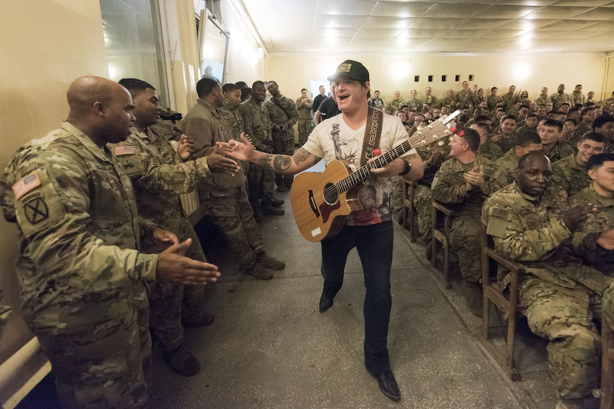 A musician high fives military personnel.