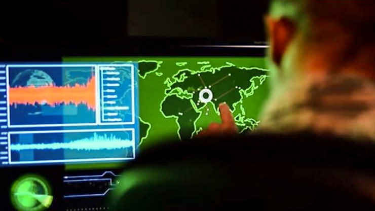 A service member, shown from behind, points to a site on a map illuminated on a monitor.