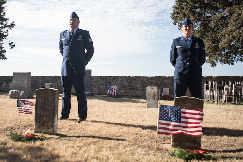 Members of the Will Rogers Air National Guard Junior Enlisted Council, Staff Sgt. David Carrillo and Airman 1st Class Brooke Evans, observe a moment of silence after laying wreaths on the graves of fallen service members at the annual Patriot Wreath Ceremony at Historic Fort Reno in El Reno, Okla., Dec. 16, 2017. (U.S. Air National Guard Photo by Senior Airman Caitlin Carnes/Released)