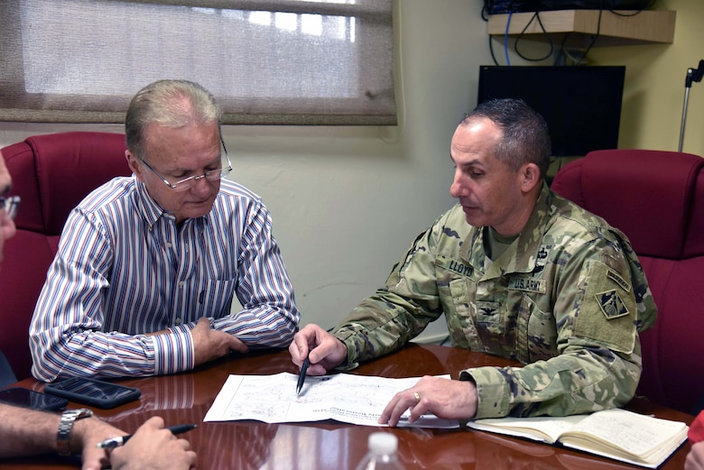 Bayamon Mayor  Ramon L. Rivera Cruz and U.S. Army Corps of Engineers Task Force Power Restoration Commander Col. John Lloyd discuss the progress of the power grid restoration while meeting at the city administration building in Bayamon, Puerto Rico, Dec. 22. The task force sought the use of city property for the storage of critical materials used in the power restoration mission, including utility poles and other power grid supplies. The city is allowing the Corps use of its property and infrastructure to help expedite delivery of needed power grid supplies and equipment across the island.